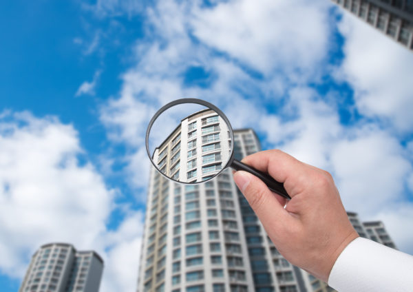 A hand holding a magnifying glass against the backdrop of an apartment.